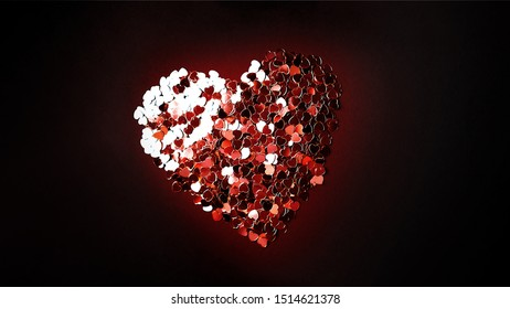 A lot of small red confetti hearts laid out on a black background in a big heart. Place for text.