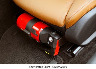 Small red fire extinguisher in the car to prevent emergencies.