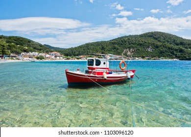 Small red fishing boat at Panormos bay in front of Panormos beach, island of Skopelos, Greece