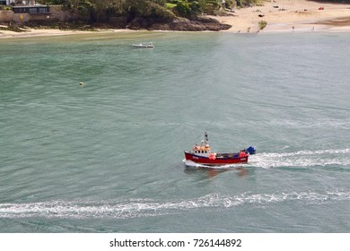 Small Red Fishing Boat Returning to Harbor