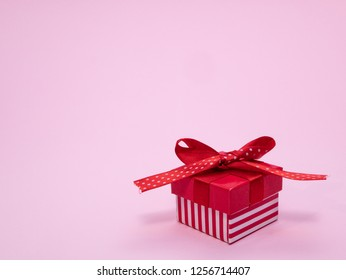 small red gift cardbox with ribbon and bow on pink background with copy space