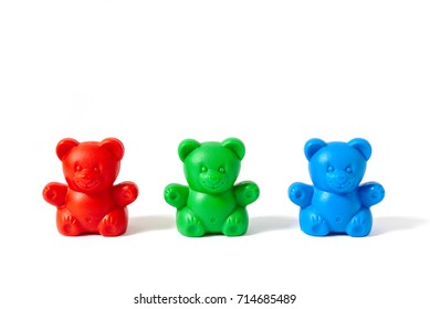 Small red, green and blue plastic toy bears isolated on white background