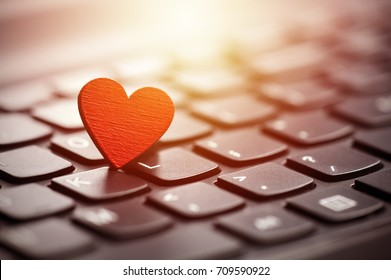 Small red heart on keyboard. Internet dating concept.