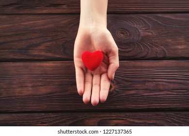 Small red heart in woman hand with copyspace