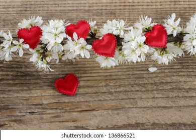 Small red hearts among cherry blossom on wooden background