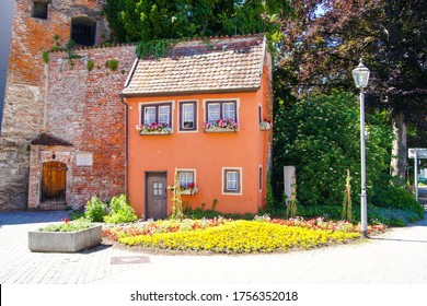 Small red house with flower boxes in front of the windows, embedded in the old brick city wall of the Bavarian town of Memmingen, Germany. A small flower field and an ancient streetlamp are in front.