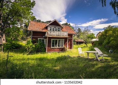 Small red house in a small island during Midsummer in the Swedish Archipelago, Sweden