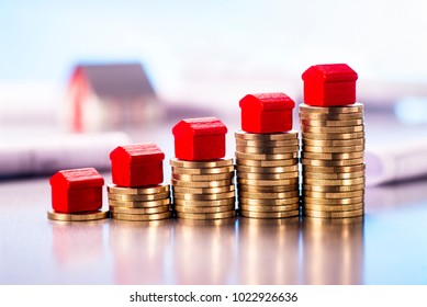 Small red houses standing on stacks of coins with blueprints and architectural model in the background.