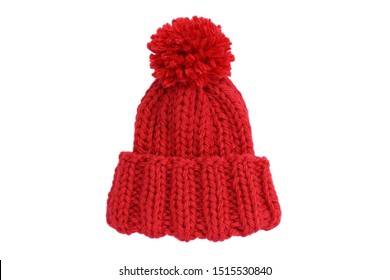 Small red knitted bobble hat isolated on a white background. Handmade woolly hat with pompom. Closeup. Copy space