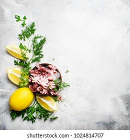 Small red octopus on the ice with green herbs and lemon, gray background, top view