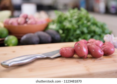 Small red potatoes on cutting board with knife in kitchen