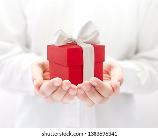Small red present box in hands