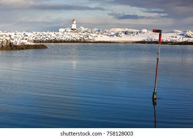Small red roofed white lighthouse-end of the breakwater marking the mouth of Hovsundhamm fishing port-N.shore of Gimsoya island-Hadseloya in background. Hovsund village-Lofoten-Nordland fylke-Norway.