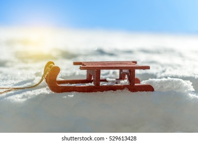 small red sled in the snow in beautiful winter day
