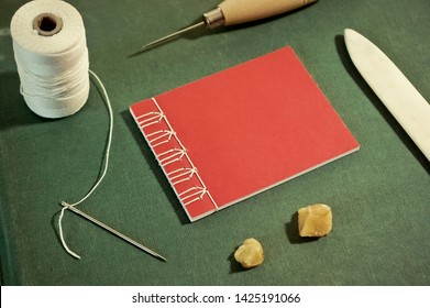 Small Red Stab Stitch Book Surrounded by Bookbinding Tools