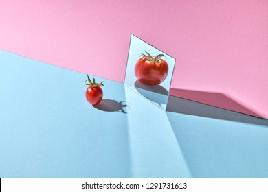 A small red tomato with a green stem is reflected large in a mirror on a blue-pink background with copy space.
