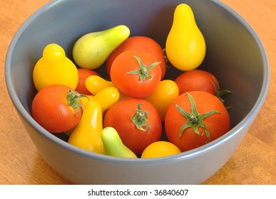Small red tomatoes with ripe and unripe yellow pear tomatoes in a bowl