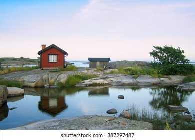 Small red wooden hut on a rocky skerry in the outer archipelago of Stockholm, Sweden. Grass in front and reflections in a small pond of water in front of the house.