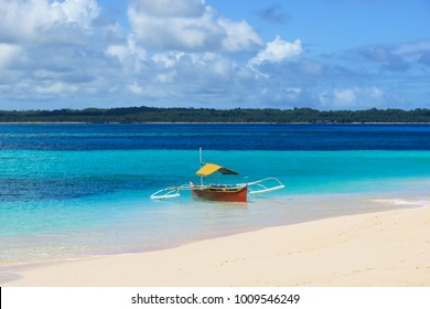 A small red and yellow wooden fishing boat on a perfect white sand beach with turqoise water - Daku Island, Siargao - Philippines