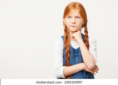 Small red-haired child girl with two long plaits thinks, looks to the left upper corner incredulously with doubt, one corner of the lips pursed, keeps fist under chin,white background,in denim overall