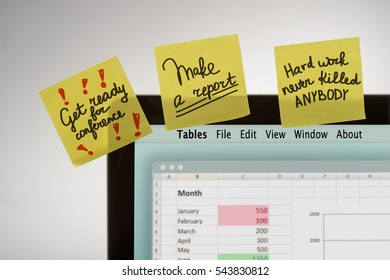 Small reminders on yellow sticky notes glued to the monitor. Organized workplace of a responsible employee with a work avalanche at his job.