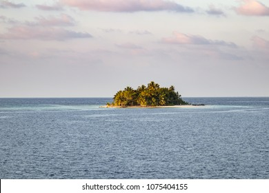 Small remote tropical island at sunset in the Pacific Ocean