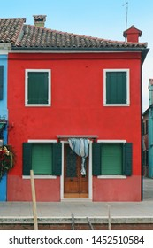 Small retro residential house with red facade and green closed windows