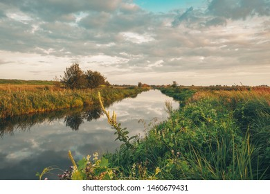 A small river flows among the mowed fields against the white clouds and the blue sky.