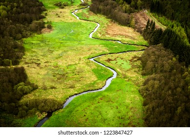 Small river going through a green area with fields and trees seen from above