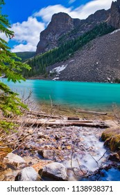 A small river streaming into the beautiful blue lake Moraine. Mountains in the background. Such a peaceful and quiet place.