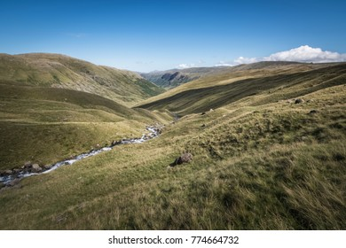 Small river swirling through the English Lake District landscape with shadow clouds casted on the grass