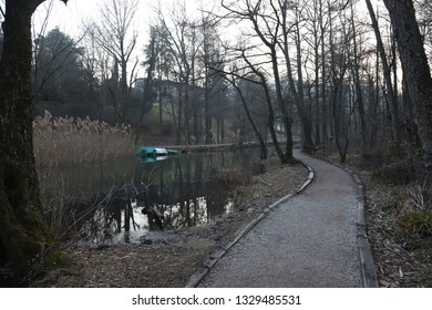 A small road in a park lies close to a river with floating boats