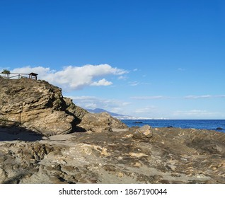 Small rock cliff on the coast with sea and sky background