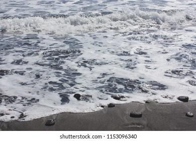Small rocks lying in black sand on the shoreline of Pololu Valley in North Kohala, Hawaii, USA