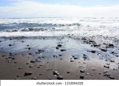 Small rocks and pebbles lying in black sand on the rocky, sandy shoreline of Pololu Valley in North Kohala, Hawaii, USA