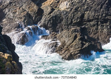Small rocky cove pounded by waves crashing onto the shore. Water crashes onto and runs off the granite that forms the coastline of North Cornwall.