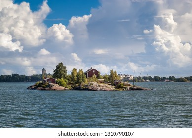 A small rocky island  in the Baltic sea near Helsinki with several red wooden houses and a small pier. View from the ferry to the island of Suomenlinna.