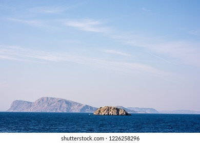 A small, rocky island juts out of a beautiful blue sea, in the Aegean Sea, near the Greek Island of Hydra.