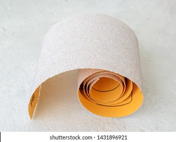 Small roll of extra coarse aluminum oxide sandpaper. Abrasive paper for dry sanding. Processing wood and metals, furniture production. On a white rough textured background. Close-up.
