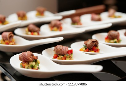 Small rolls of roast beef with vegetables on banquet table
