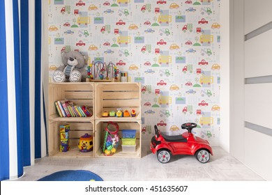 Small room with colorful wallpaper designed for boy. By the all wooden shelves with toys and little car
