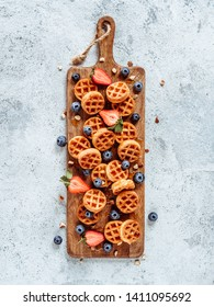 Small round delicious soft belgian waffles on cutting board. Fresh belgian waffles with berries and caramel sauce top view. Copy space for text or mock up. Vertical