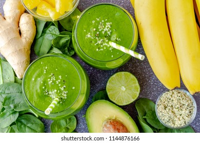 Small round glasses filled with green kale and spinach smoothie and green swirled straws surrounded by ingredients