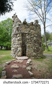 Small round structure made of rocks with an opening.  There is a path leading up to the entrance to the structure.