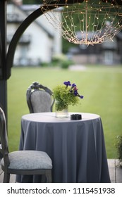 A small round table with a tablecloth and soft chairs stands under a canopy on the lawn near the house