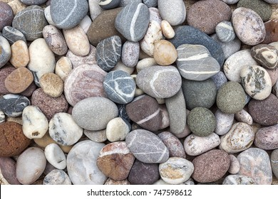 Small rounded beach pebbles or smooth rocks with various colors and shapes of stones, overhead view.