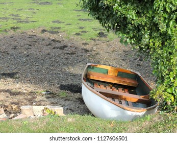 Small row boat moored by the side of a river at low tide.