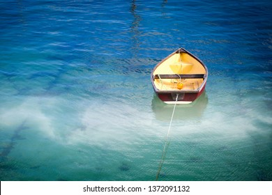 Small rowboat in the blue water