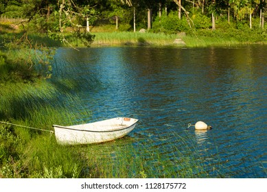 Small rowboat in a summer forest lake. Location Stansjo in Smaland, Sweden.