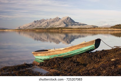 Small rowing boat laying on rocks covered by seaweed. Mountains on background reflecting on water surface. Photographed in Helgeland, Norway.